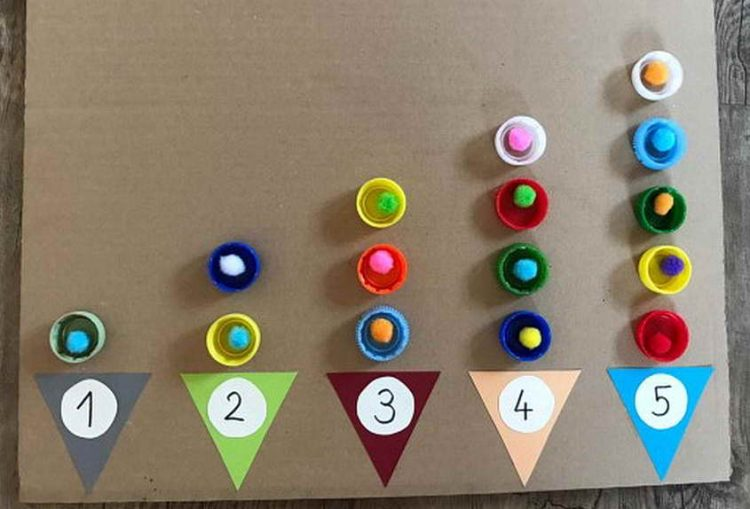 """Bei diesem Lernarrangement befüllen die Kinder """"Eistüten"""" mit einer bestimmten Anzahl an Eiskugeln. Die Verschlüsse von PET-Flaschen können dabei beispielsweise als Auffang-behälter genutzt werden. (Julia Aunitz)"""